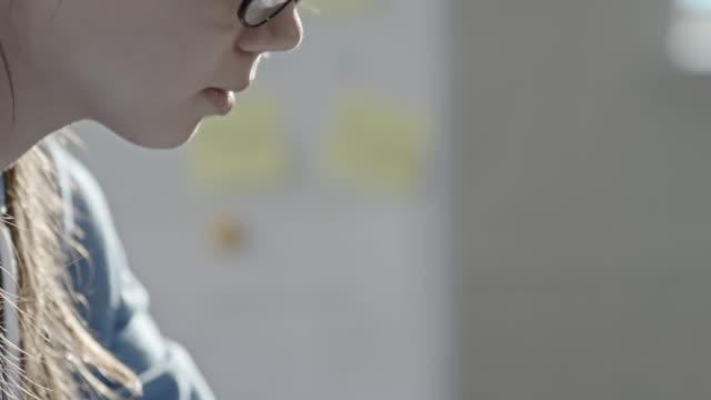 Girl in glasses doing homework on laptop