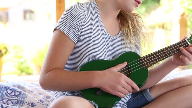 stockvideo's en b-roll-footage met girl in hammock, playing a ukulele - korte broek