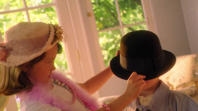 MS girl in hat playing dress-up putting hat on boy over his eyes + hugging him indoors