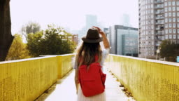 Girl in hat with long hair walks on a city bridge. Caucasian woman between yellow walls with red backpack. Back view 4K