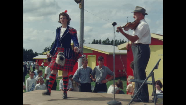 girl in kilt and scottish dress highland dancing as man plays the fiddle - danza tradizionale video stock e b–roll