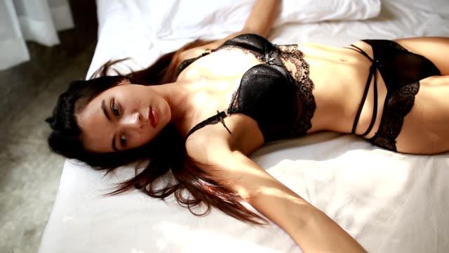 vídeos de stock, filmes e b-roll de garota em lingerie, deitado em sua cama - tronco termo anatômico