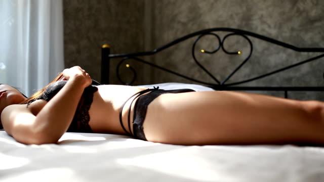 Girl in lingerie lying in her bed