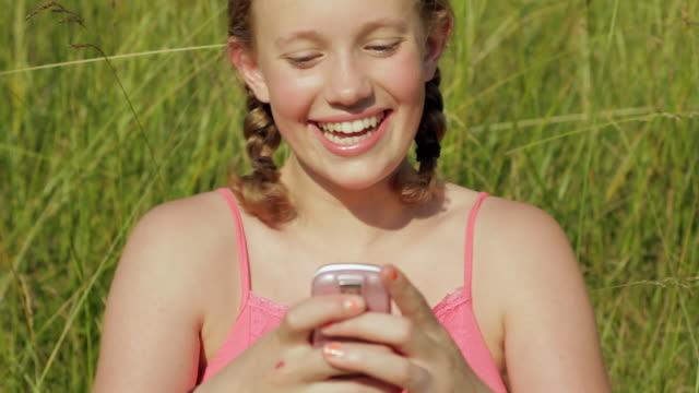 cu girl (12-13) in meadow text messaging / glen gardner, new jersey, usa - 12 13 år bildbanksvideor och videomaterial från bakom kulisserna