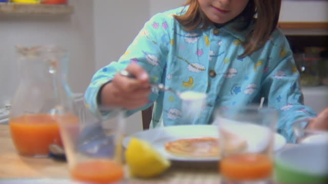 MS Girl in pajamas at breakfast table putting lemon juice and sugar on pancake, rolling it up, and eating it/ Rome, Italy