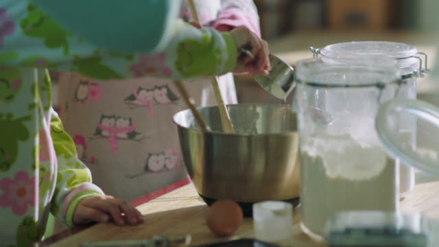 CU. Girl in pajamas dumps cup of flour into mixing bowl while fixing breakfast in the kitchen with her family.