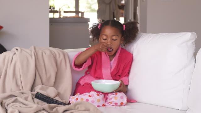 ws girl (4-5) in pajamas sitting on sofa, eating breakfast, phoenix, arizona, usa - pajamas stock videos & royalty-free footage