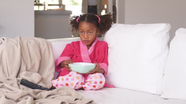WS Girl (4-5) in pajamas sitting on sofa, eating breakfast, Phoenix, Arizona, USA