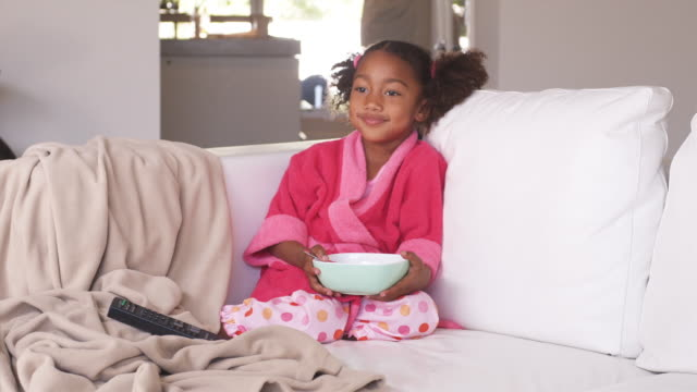 ws girl (4-5) in pajamas sitting on sofa, eating breakfast, phoenix, arizona, usa - pyjamas stock videos & royalty-free footage