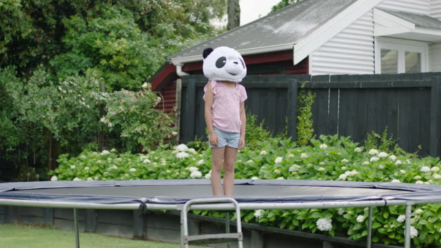 girl in panda mask standing on trampoline - pedana elastica per saltare video stock e b–roll