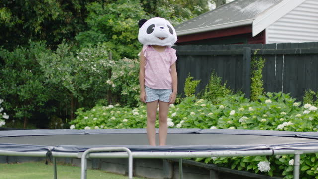 girl in panda mask standing on trampoline - domestic garden stock videos & royalty-free footage