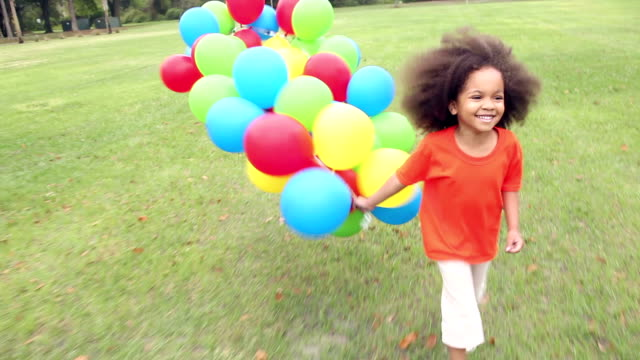 Girl in park running with big bunch of colorful balloons
