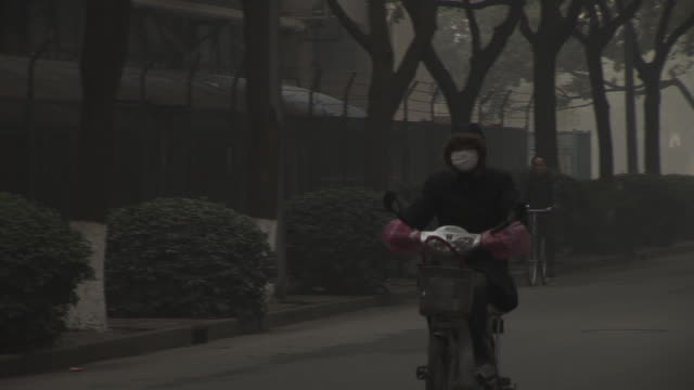 WS Girl in parka and pollution mask riding scooter up to employee entrance to Shanghai Pudong International Airport/ PAN MS Security guard giving girl ticket to enter gate/ Shanghai, China
