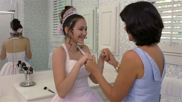 Girl in Quinceanera dress and mother holding hands in bathroom