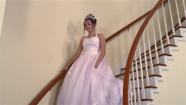 girl in quinceanera dress descending staircase - cerimonia tradizionale video stock e b–roll