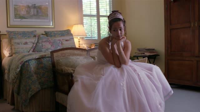 girl in quinceanera dress sitting on love seat in bedroom - 少女のみ点の映像素材/bロール