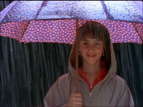 vidéos et rushes de girl in raincoat holding large umbrella in rain + smiling at camera - vêtement de pluie