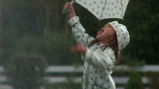 MS Girl in raincoat holding umbrella playing on street during rain / Richmond, Virginia, USA