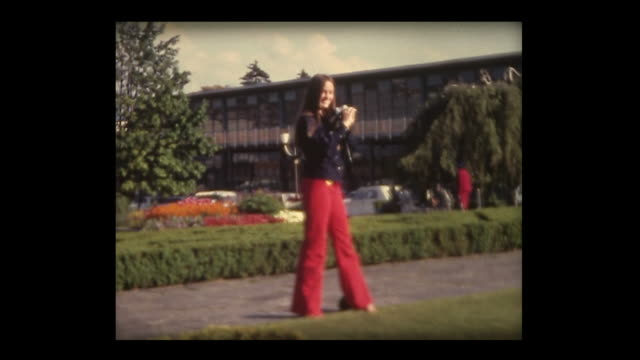 1972 girl in red pants takes picture of fountain - weiblicher teenager stock-videos und b-roll-filmmaterial