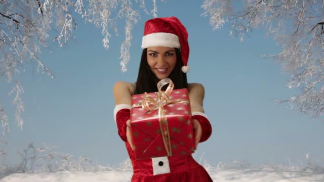 girl in red santa hat giving gift - santa hat stock videos & royalty-free footage