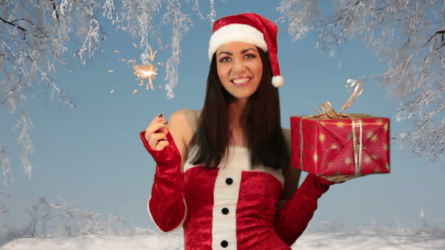 girl in red santa hat holding Christmas Present
