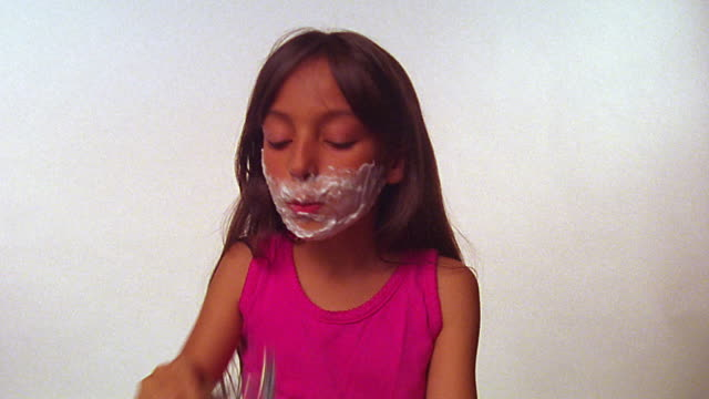 vídeos de stock, filmes e b-roll de ms girl in red tank top shaving her face + with razor + shaving cream / white background - raspando