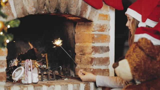4K Girl in Santa hat lighting sparkler at Christmas fireplace, real time