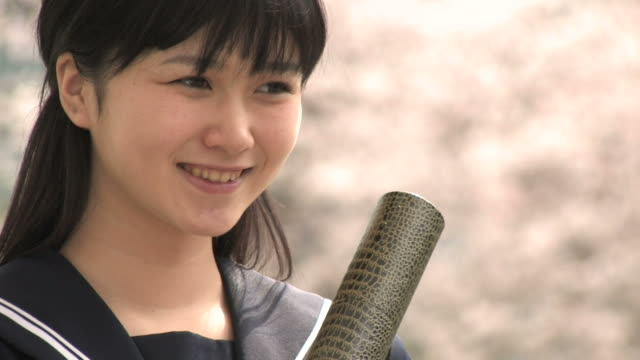 girl in school uniform smiling, holding graduation certificate - japanese school uniform stock videos & royalty-free footage