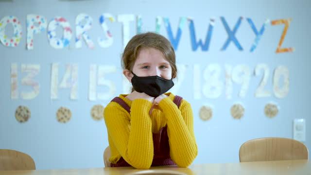 学校の女の子、フェイスマスクを着用 - 座る点の映像素材/bロール