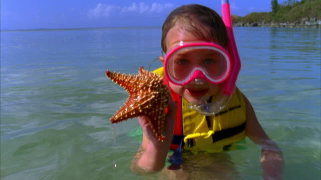 CU, Girl (6-7) in snorkeling gear playing with starfish in sea, Vieques, Puerto Rico