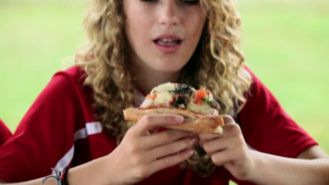 girl in soccer kit, eating a slice of pizza - slice stock videos & royalty-free footage