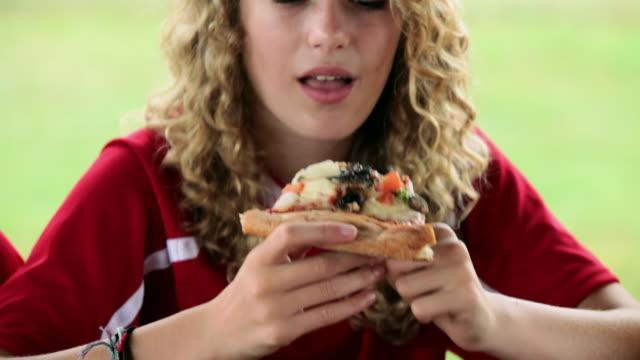 stockvideo's en b-roll-footage met girl in soccer kit, eating a slice of pizza - alleen één tienermeisje