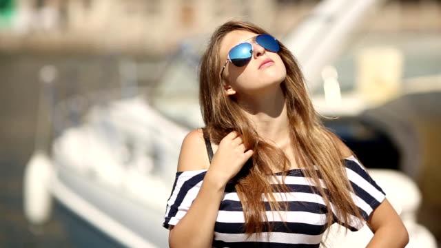 girl in sunglasses posing near the yacht
