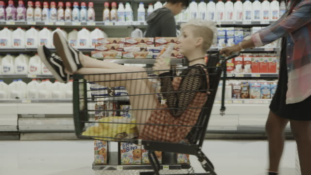 vídeos y material grabado en eventos de stock de girl in supermarket pushing friend sitting in shopping cart / provo, utah, united states - provo