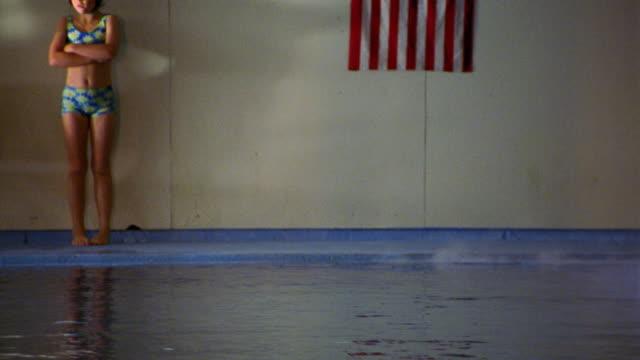 vídeos y material grabado en eventos de stock de pan girl in swimsuit + goggles standing with arms crossed by indoor pool / american flag on wall - traje de baño de una pieza