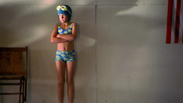 Girl in swimsuit, swim cap + goggles standing with arms crossed at side of indoor pool looking sad