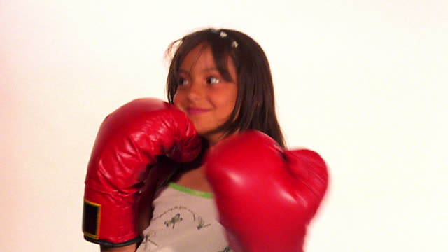CANTED MS PORTRAIT girl in tank top with oversized boxing gloves posing + rolling eyes / white background