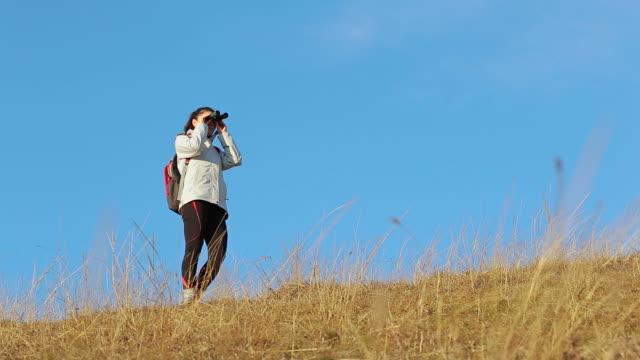 女性の自然の丘を探索。 - 双眼鏡点の映像素材/bロール