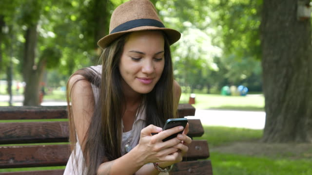 Girl in the park taking selfie and texting