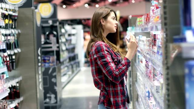 vidéos et rushes de une fille dans le supermarché - produit de beauté