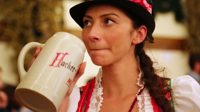 cu girl in traditional croatian dress talking and drinking from beer jug at traditional oktoberfest / munich, bavaria, germany  - beer stein stock videos and b-roll footage