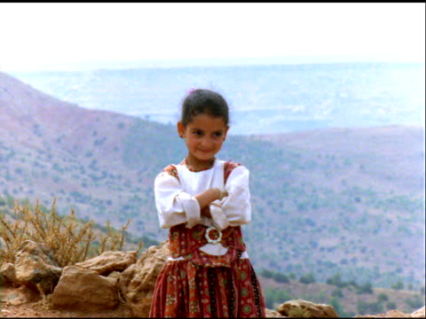girl in traditional dress on hillside, smiling at camera, morocco - menschliche gliedmaßen stock-videos und b-roll-filmmaterial