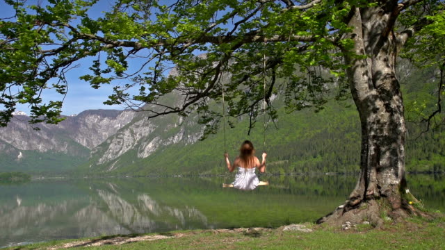 girl in white dress on a swing by the lake - white dress stock videos & royalty-free footage
