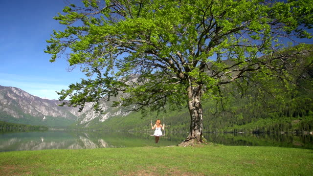 girl in white dress on rope swing by the lake - mgost stock videos and b-roll footage