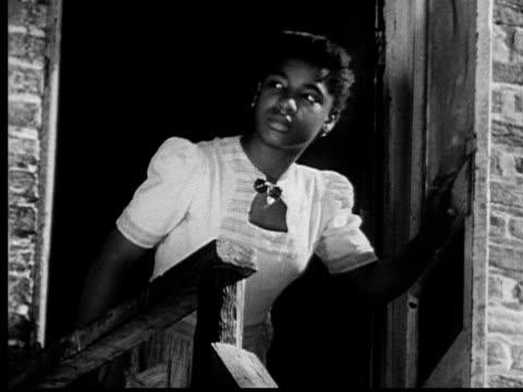 vidéos et rushes de 1953 ms girl in white dress opening door, looking outside, and closing door/ baltimore, maryland - 1953