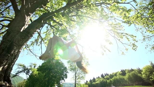 Girl in white dress spinning on rope swing under tree