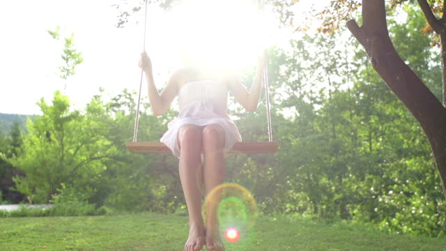 Girl in white dress swinging on a rope swing