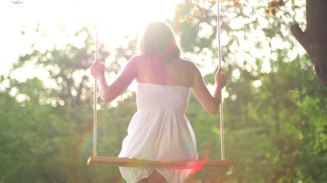 Girl in white dress swinging on a rope swing