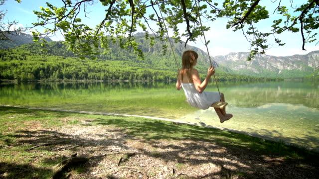 girl in white dress swinging on rope swing by lake - rope swing stock videos & royalty-free footage