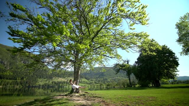 girl in white dress swinging on rope swing under tree - mgost stock videos and b-roll footage